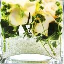Gele bloemen in glas water